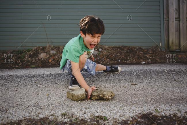 Boy imitating to break stones while practicing karate on street