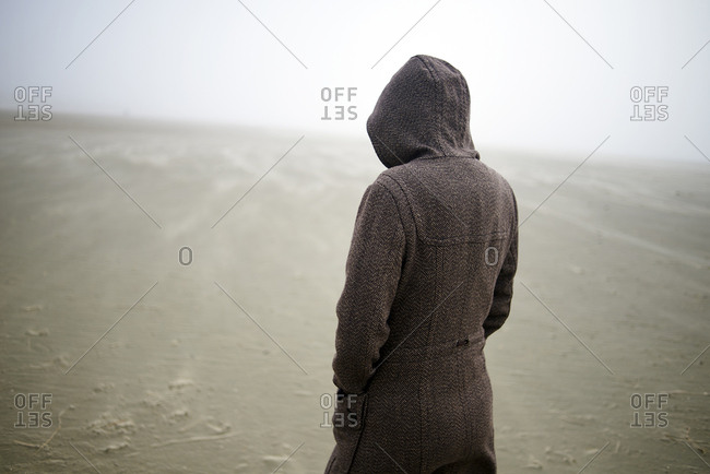 Woman wearing hooded coat at beach during foggy weather