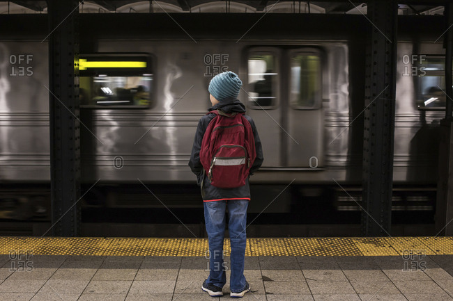 Full length rear view of boy with backpack standing at subway station