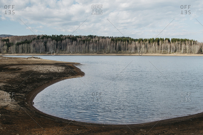 Scenic view of calm Lake Vlasina against cloudy sky in forest