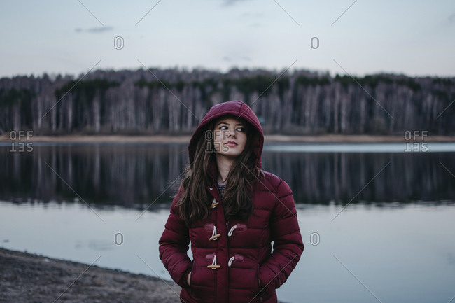 Woman looking away while standing by Lake Vlasina against sky during sunset