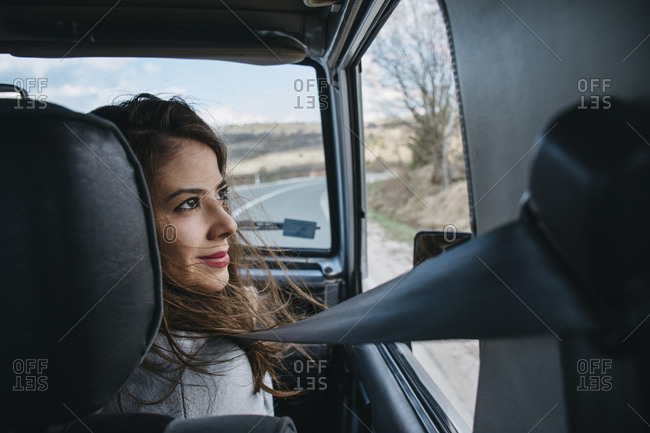 Rear view of smiling woman looking through window while traveling in car