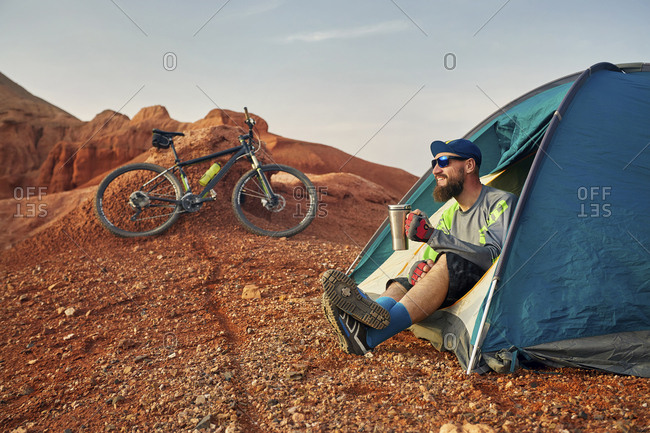 Hiker having coffee while sitting in tent at desert