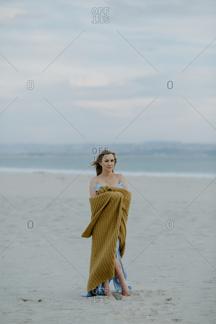 Portrait of woman holding scarf while standing at beach against cloudy sky