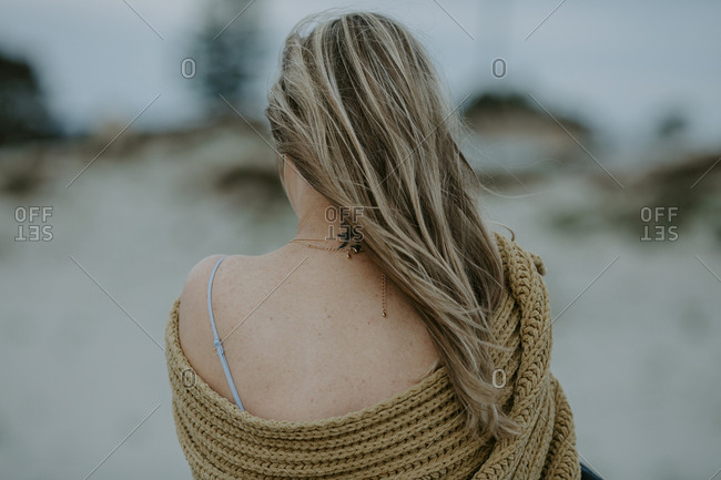 Rear view of woman with scarf standing at beach against sky