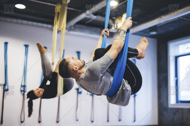 Friends hanging on hammocks while practicing aerial yoga in gym