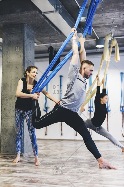 Yoga instructor assisting man while woman exercising in background at gym