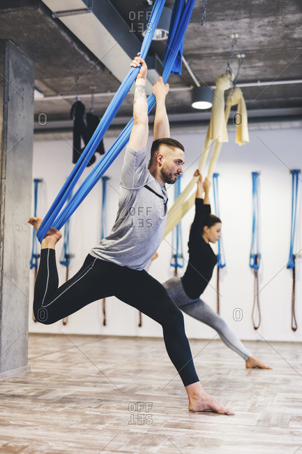 Friends stretching using hammocks while practicing aerial yoga in gym