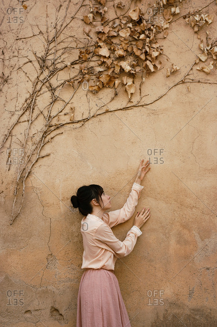 Side view of woman in tender light outfit crawling hands on shabby wall with drying branches and leaves above