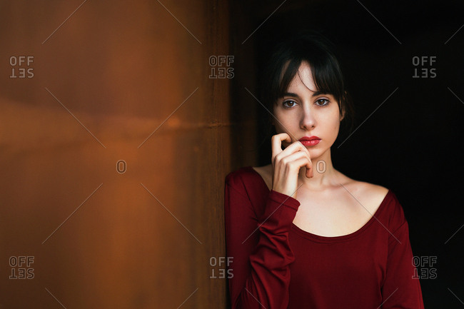 Young emotionless brunette wearing elegant red outfit looking at camera while touching face and leaning on wall