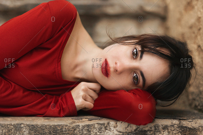 Amazing sensual model in red dress lying on stone step looking at camera
