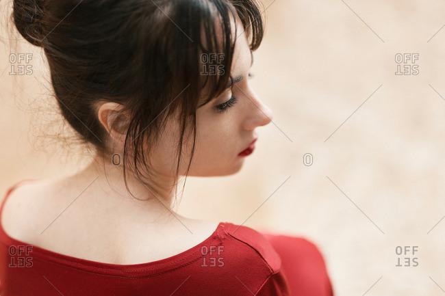Tender girl in red looking away