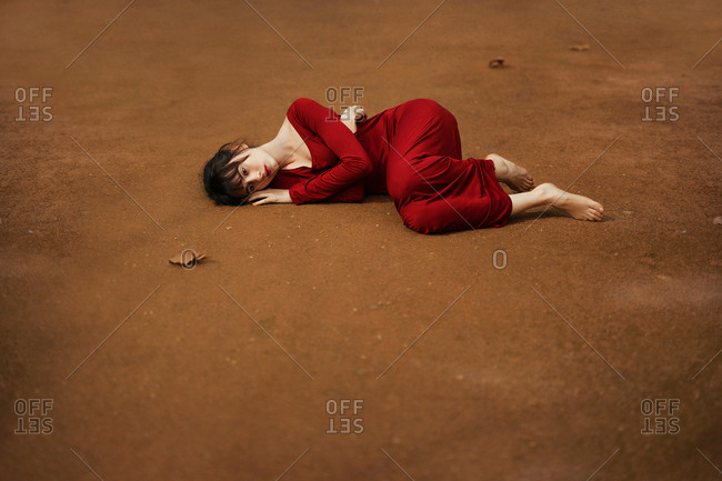 Skinny brunette wearing red dress and lying barefoot on brown ground crouched