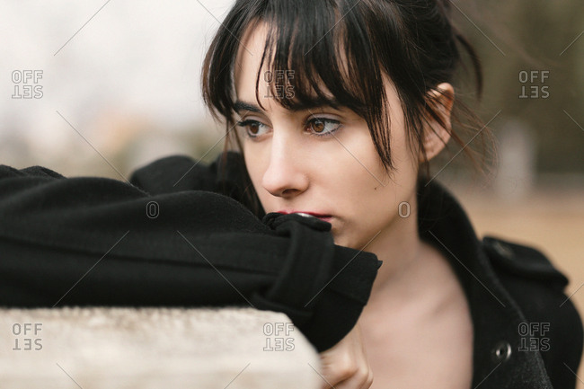 Melancholic woman in black leaning on fence