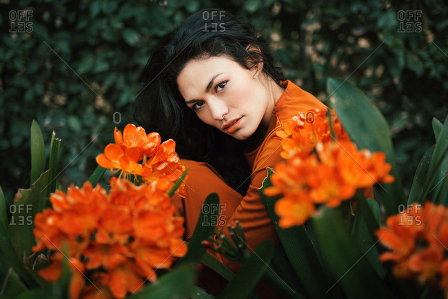 Attractive young woman looking at camera and sitting in bright orange flowers