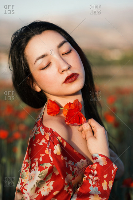 Gorgeous model in red dress holding poppy flowers