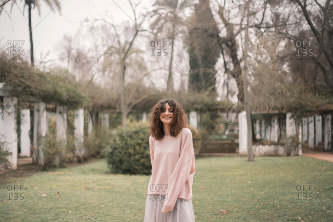 Stylish curly brunette in sweater and skirt smiling charmingly at camera standing on lawn in garden alley