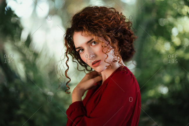 Side view of alluring beautiful woman with curls wearing red dress and posing sensually on green