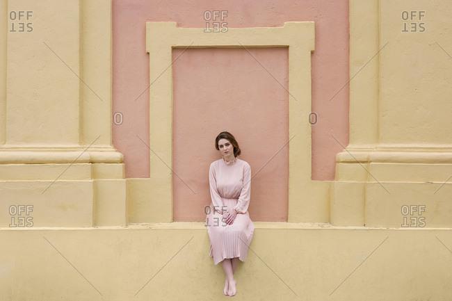 Woman in pink dress posing at wall