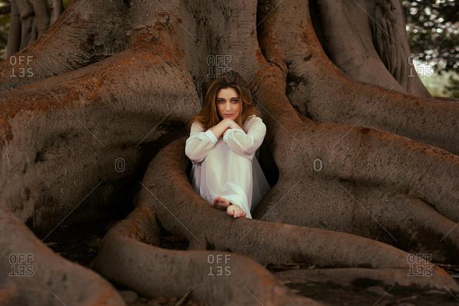 Woman looking at camera at tree