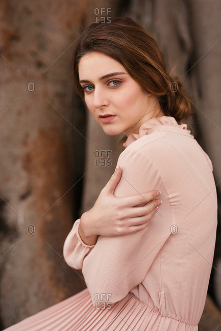 Attractive woman in pink vintage dress looking at camera and sitting at huge tree