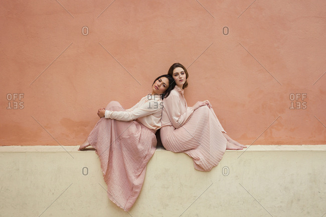 Side view of pretty women in vintage dresses sitting back to back at orange wall