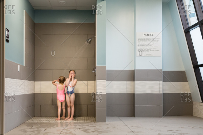 Two girls bathing in swimsuits in a public shower