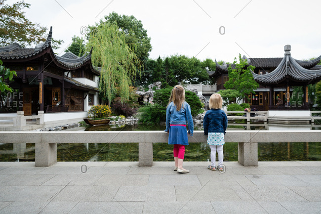 Two girls looking at pond in Asia