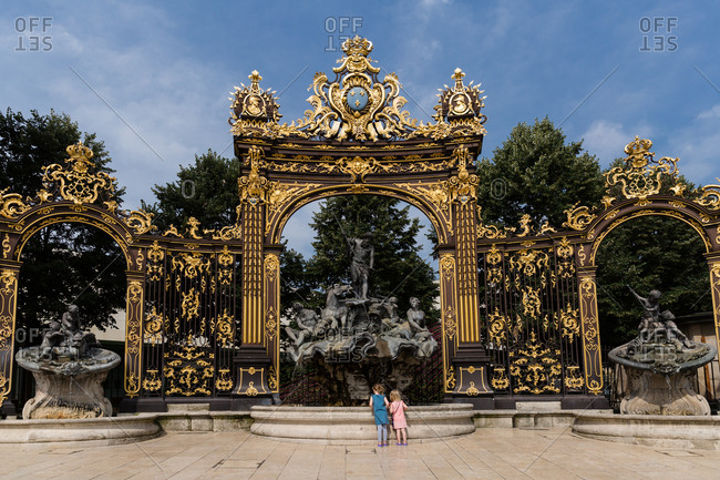 Two girls looking in fountain at Place Stanislas