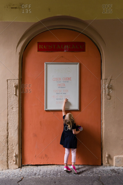 Rear view of little girl touching menu board on restaurant door