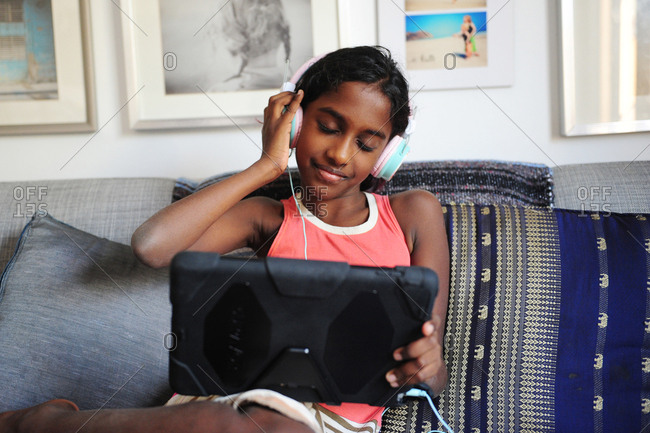Girl listening to music with headphones and a tablet