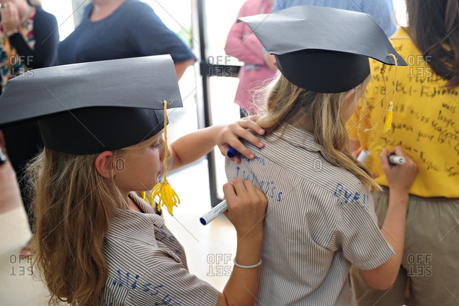 School girls signing each other's shirts at graduation