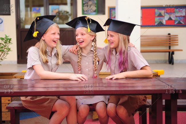 Three girls hugging on graduation day