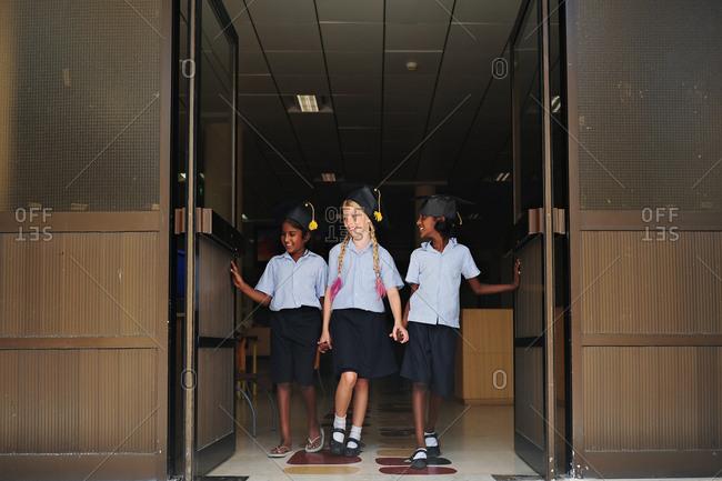 Three girls walking through doors after graduation