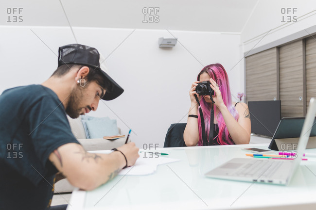 Young woman with pink hair photographing a young man drawing