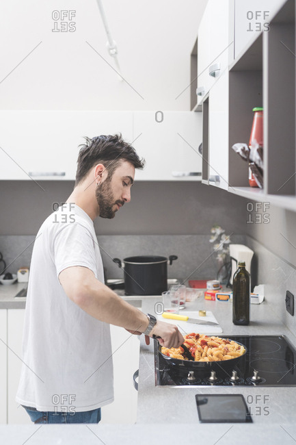 Young man at home cooking and stirring