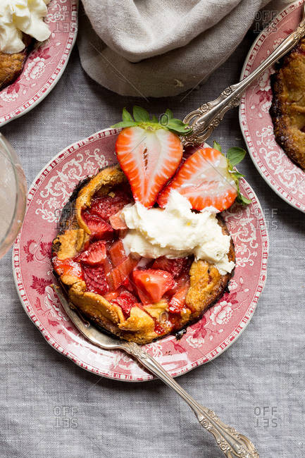 Gluten-free strawberry rhubarb pie on vintage china with rosette wine