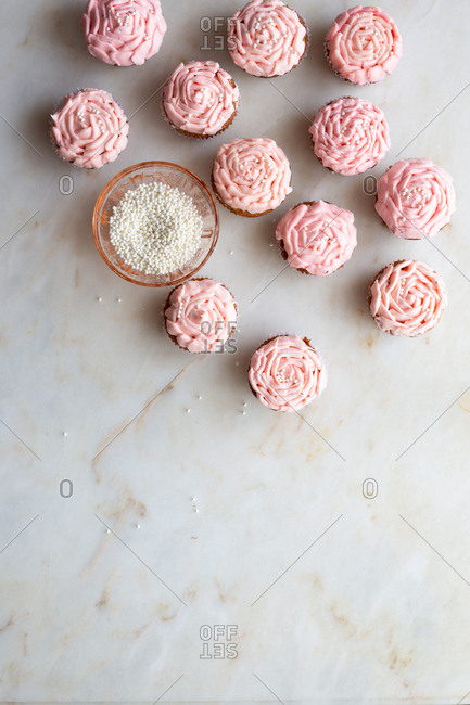 Pink cupcakes with decorations on marble background