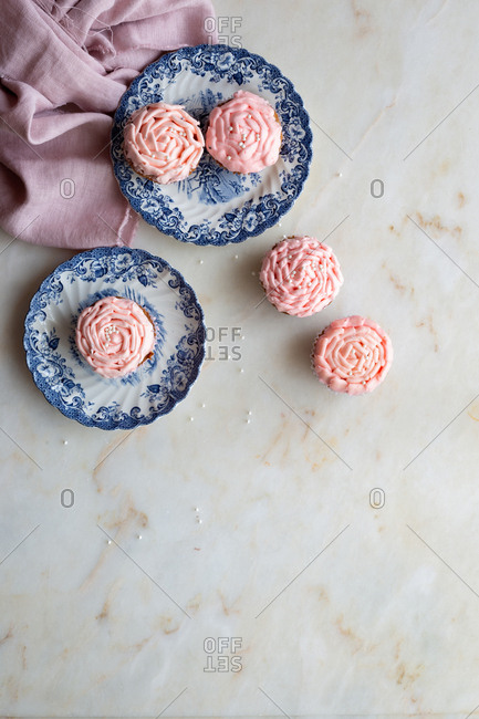 Light pink cupcakes on china plates