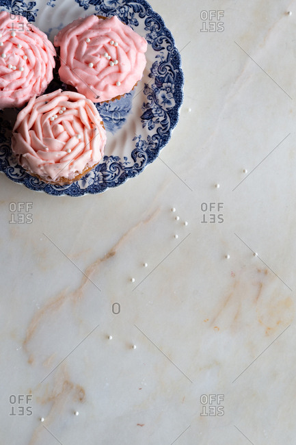 Plate of pink cupcakes on marble background