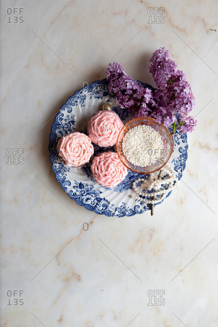 Light pink cupcakes with lilacs on marble background