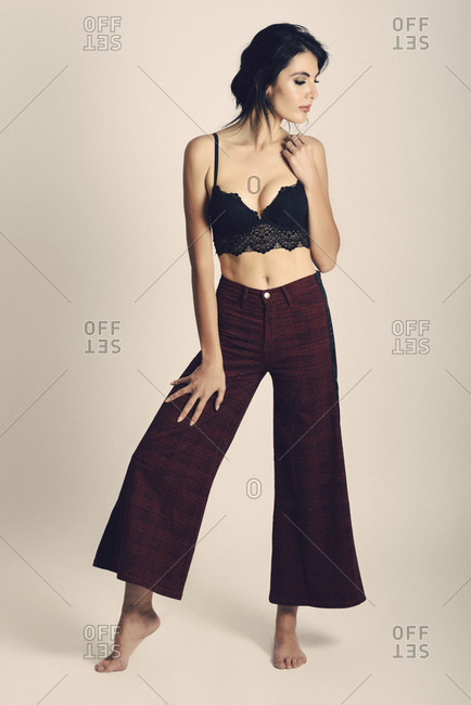 Woman poses against white background wearing modern trousers and elegant black bra