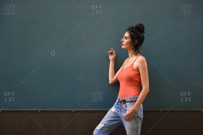 Profile view of woman with eyes closed wearing casual clothes on blue urban wall