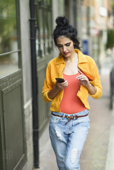 Woman looking at a smart phone while walking down the street