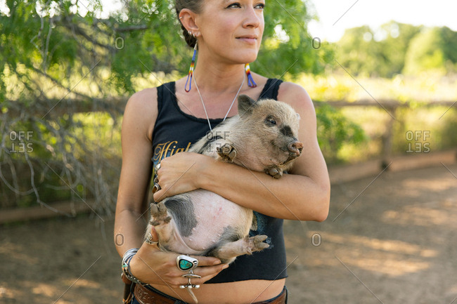 Young woman holding spotted baby pig