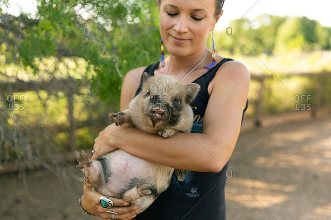 Woman holding spotted baby pig