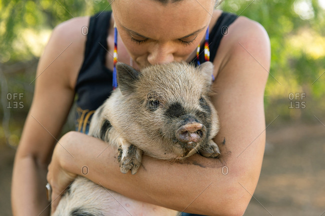 Woman holding and kissing a spotted baby pig