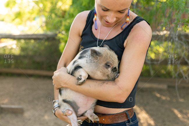 Close up of a young woman holding spotted baby pig
