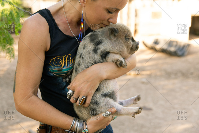 Young woman holding and kissing a spotted baby pig