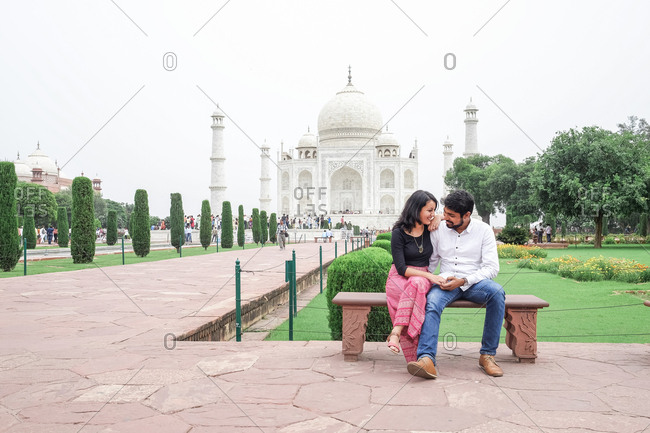 Couple sitting in front of the Taj Mahal